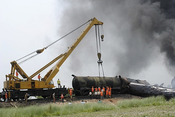 Workers remove damaged oil tankers from rail tracks in Chintawanpur in Bihar